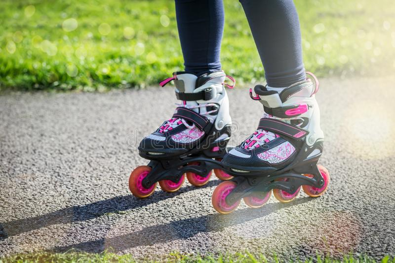 Teenage girl is skating on roller blades in the park royalty free stock images