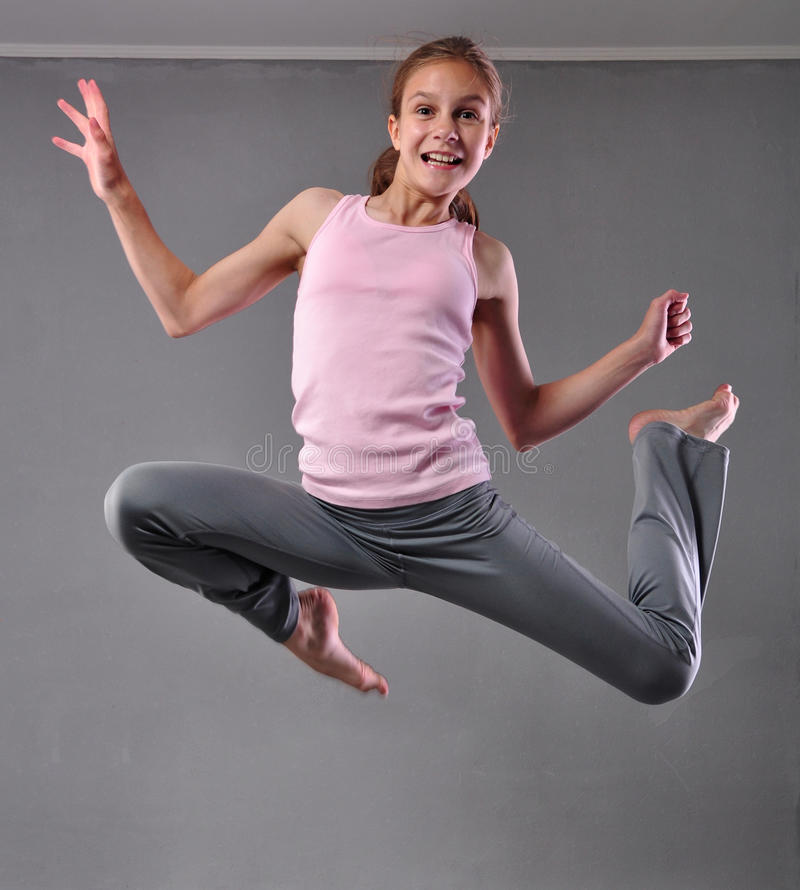 Teenage girl skipping and dancing in studio. Child exercising with jumping on grey background. royalty free stock photos