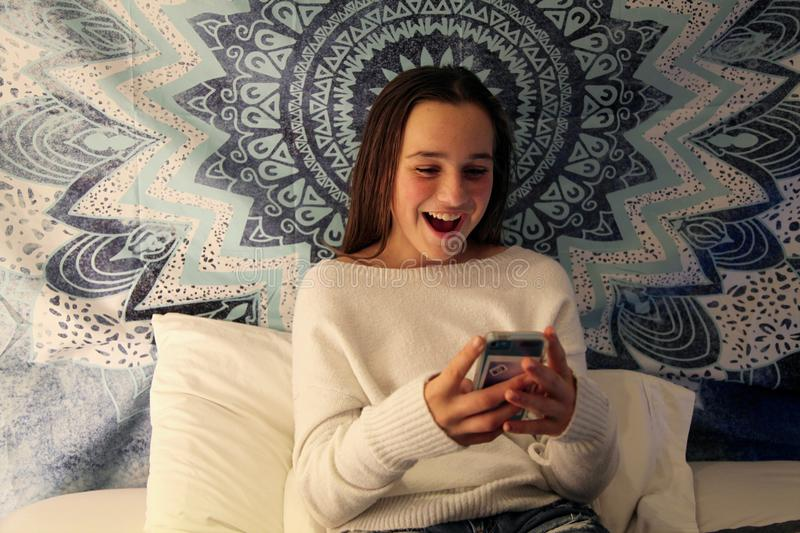 Teenage girl smiling at her mobile phone while texting royalty free stock images