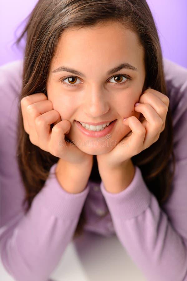 Teenage girl smiling on purple close-up portrait stock photo