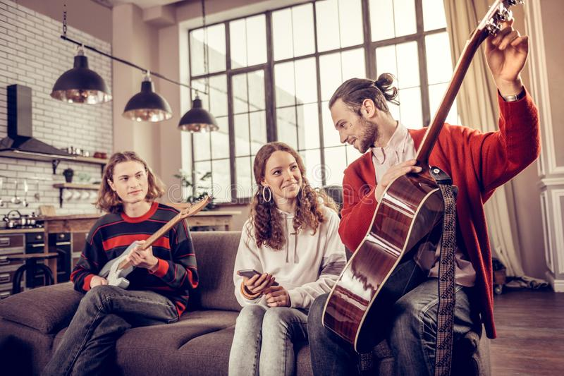 Teenage girl spending time with her brothers playing the guitar royalty free stock images
