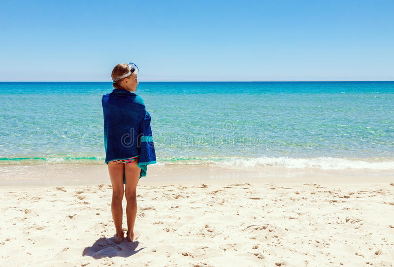 Teenage girl standing alone on the beach. Young teenage girl standing alone on the beach at summer. Covered with towel and wearing snorkel glasses on her head stock photography