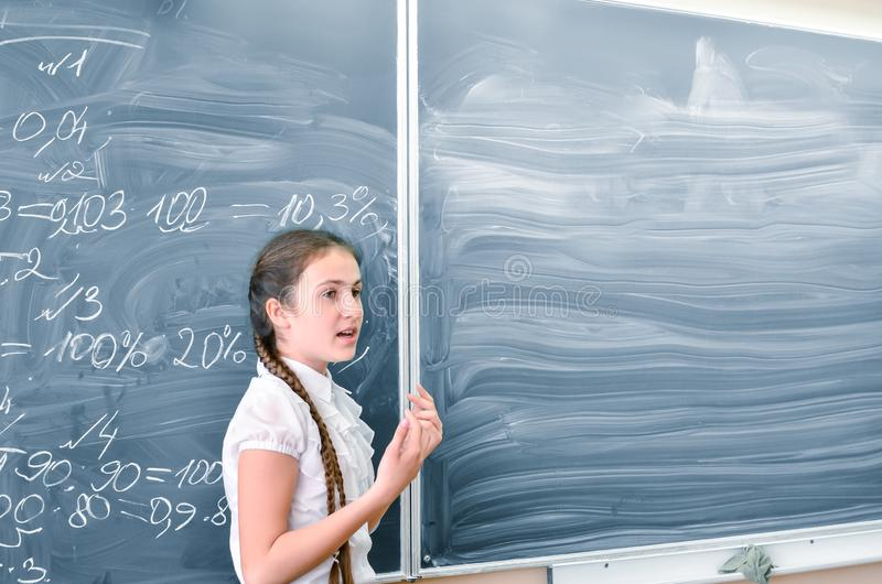 Teenage girl standing and answering at the blackboard in math class. Education, back to school concept, copy space. stock photos