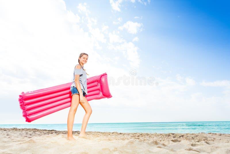 Teenage girl standing with matrass on sandy beach royalty free stock image