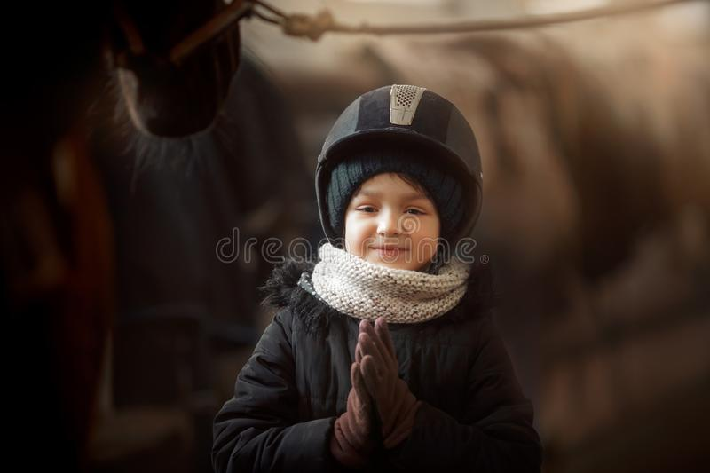 Teenage girl standing with horse in a stable stock photos