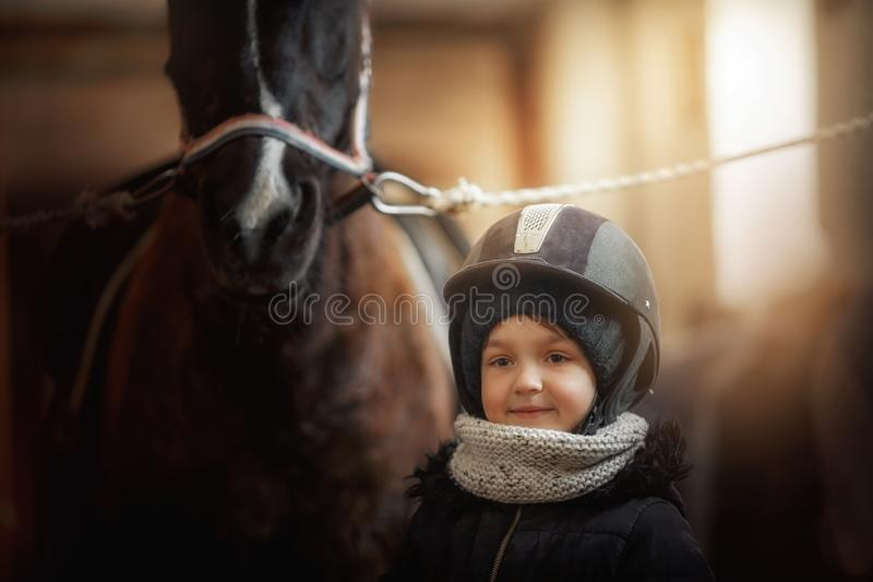 Teenage girl standing with horse in a stable stock images