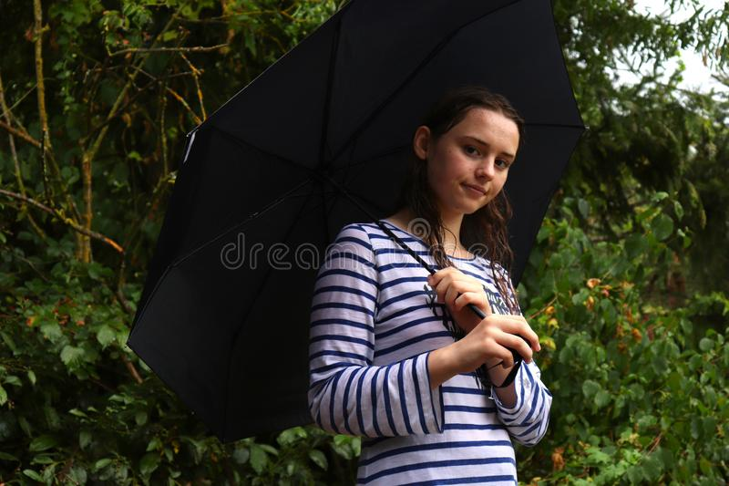 Teenage girl standing under an umbrella in the rain stock photo