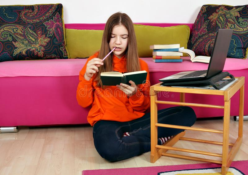 Teenage girl studies with a laptop and a book royalty free stock photography