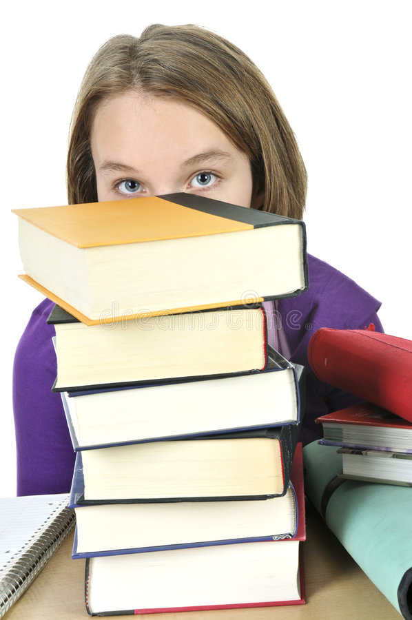 Teenage girl studying. Frustrated teenage girl studying at the desk with big stack of books stock images