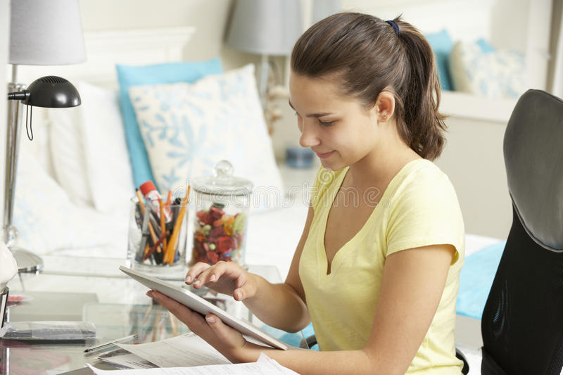 Teenage Girl Studying At Desk In Bedroom Using Digital Tablet royalty free stock images