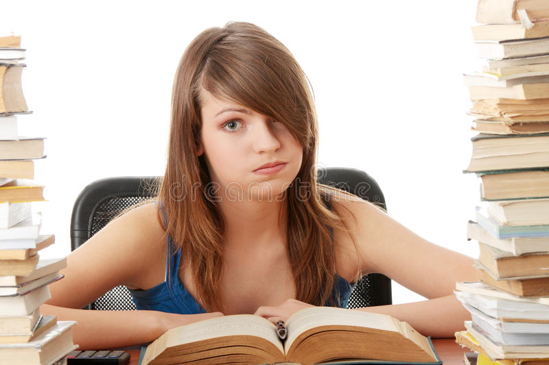 Teenage girl studying at the desk being tired stock image