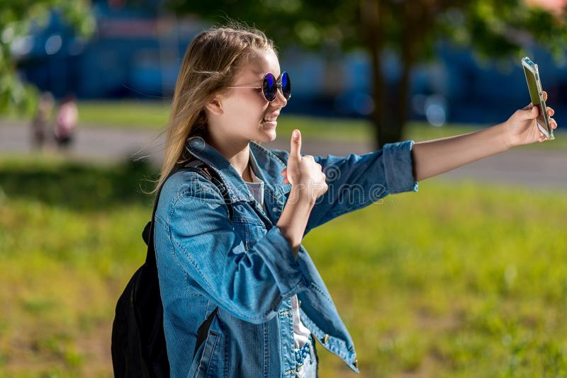 A teenage girl, summer in nature. In hands of holding a smartphone, sends greetings to the video call. With a gesture of stock images