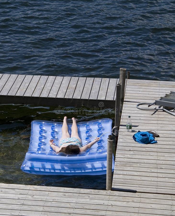 Teenage Girl Sunbathing on Raft at Lake royalty free stock image