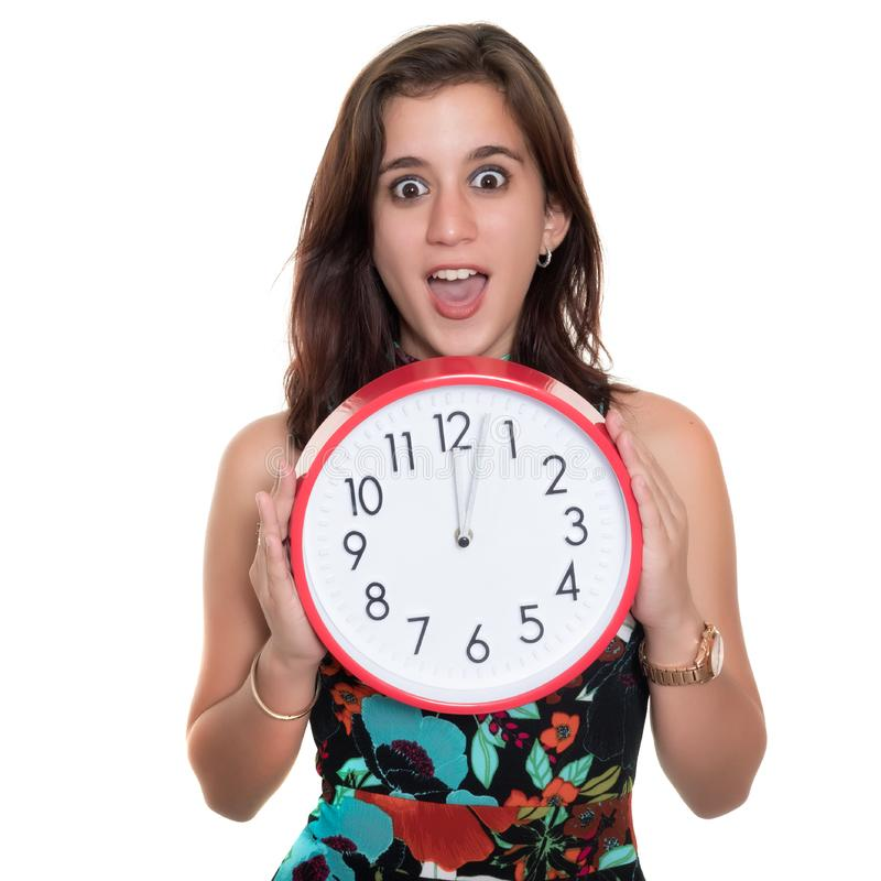 Teenage girl with a surprised expression showing the time on a big clock royalty free stock image
