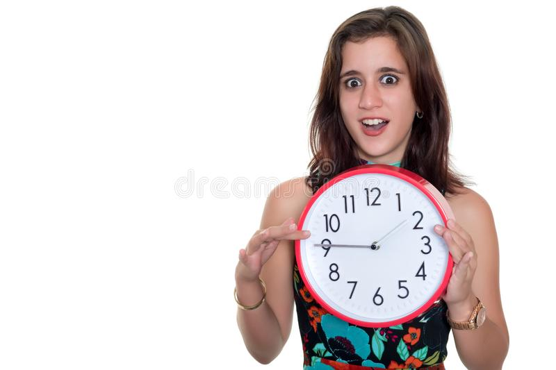 Teenage girl with a surprised expression showing the time on a big clock royalty free stock photo