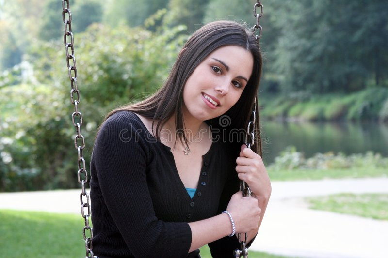 Teenage girl on swing. A very pretty teenage girl sitting on a park swing royalty free stock photography