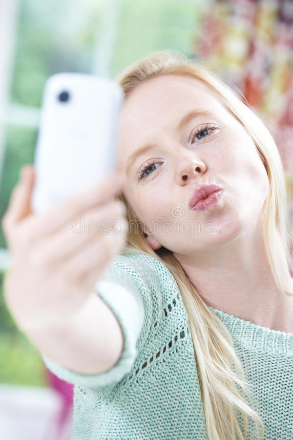 Teenage Girl Taking Selfie On Mobile Phone. Funny Teenage Girl Self Harming With Knife Blade stock photography