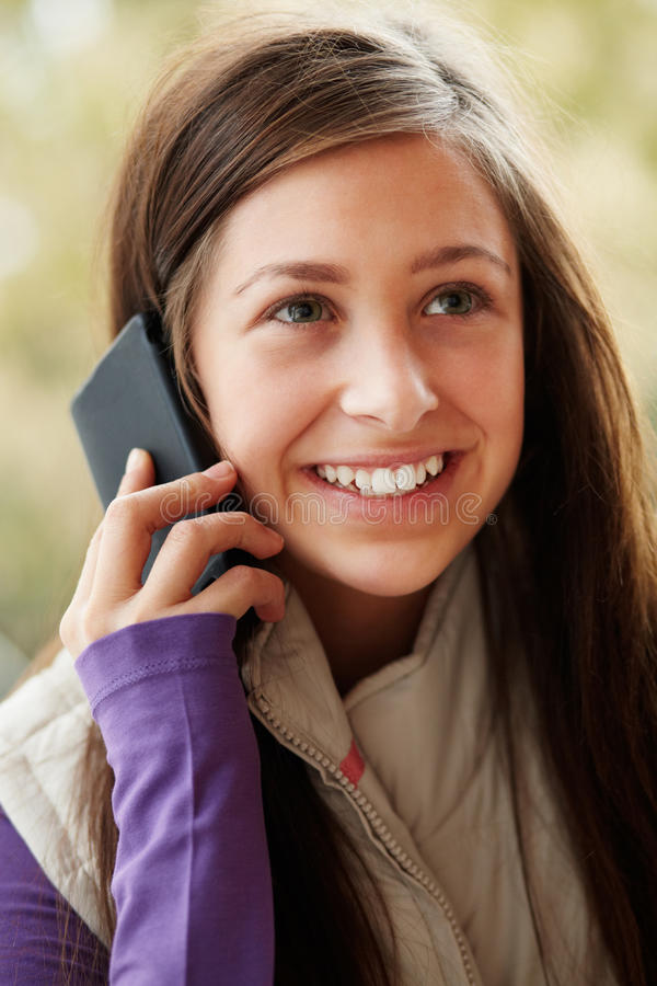 Teenage Girl Talking On Smartphone. Wearing Winter Clothes stock photography
