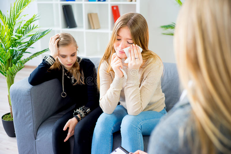 Teenage girl during therapy session. Teenage girl sitting on sofa during therapy session while therapist is taking notes royalty free stock image