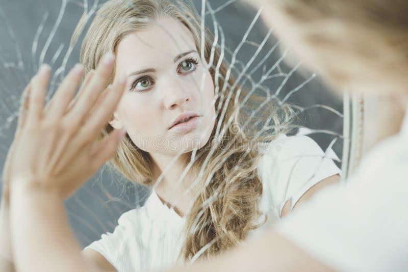 Teenage girl touching broken mirror. Teenage girl with personality disorder touching broken mirror stock images