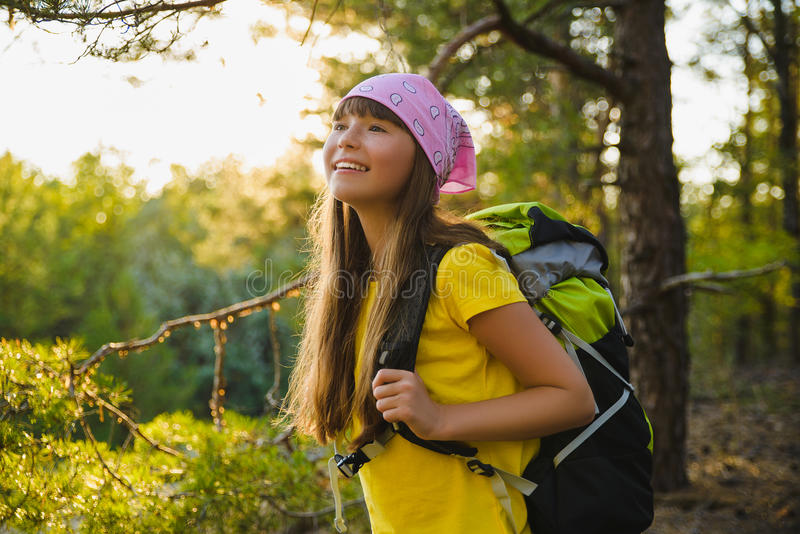 Girl traveler with backpack in hill forest. Adventure, travel, tourism concept stock photography