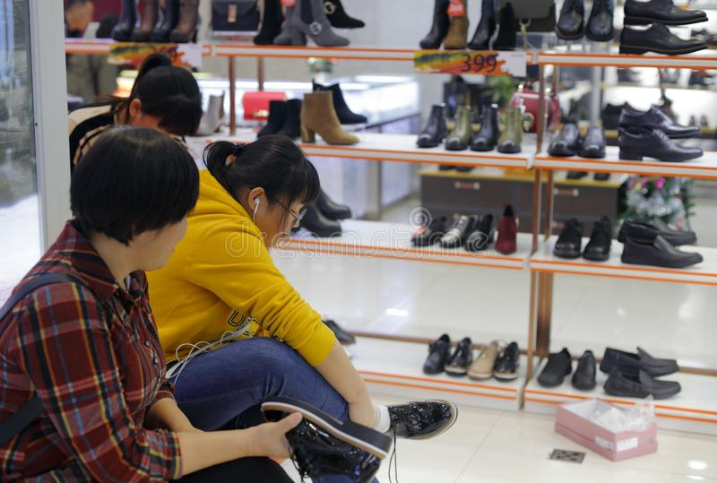 Teenage girl trying on shoes, adobe rgb stock photos
