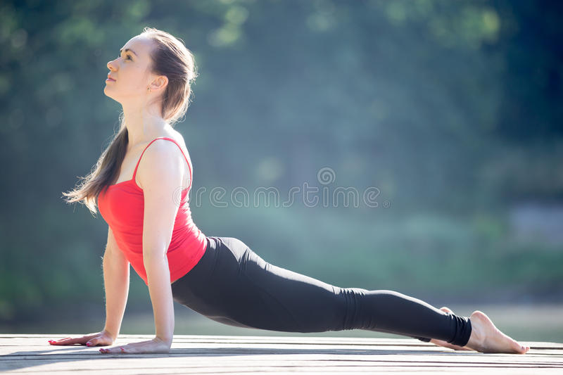 Teenage girl in Upward facing dog pose. Beautiful sporty fit young woman in sportswear working out outdoors on summer day, doing exercise for back, urdhva mukha stock images