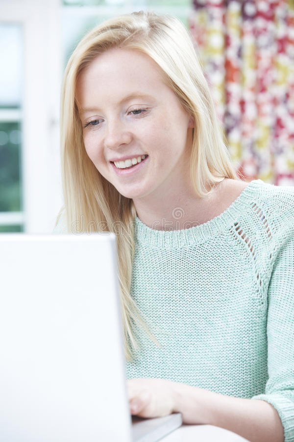 Teenage Girl Using Computer At Home. Happy Teenage Girl Using Computer At Home stock photography