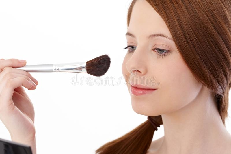 Teenage girl using makeup brush smiling. Teenage ginger girl using makeup brush, smiling stock photography
