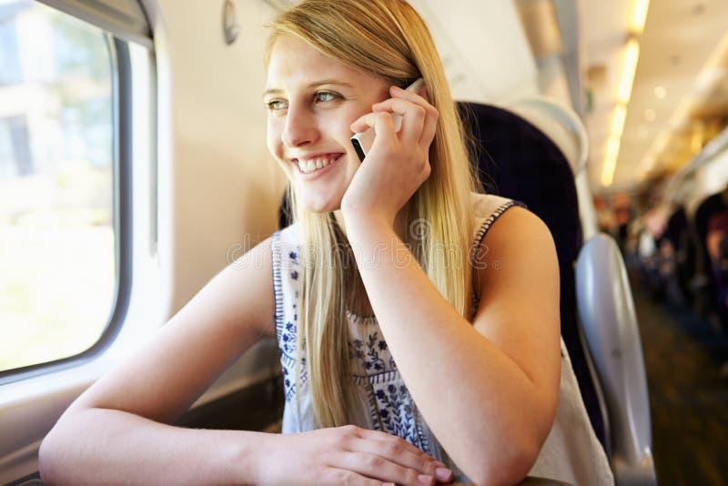Teenage Girl Using Mobile Phone On Train Journey royalty free stock photos