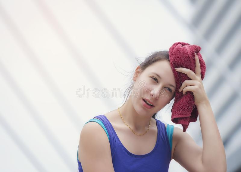 A teenage girl is using a towel on her head after exhaustion. A teenage girl is using a towel on her head after exhaustion royalty free stock photography