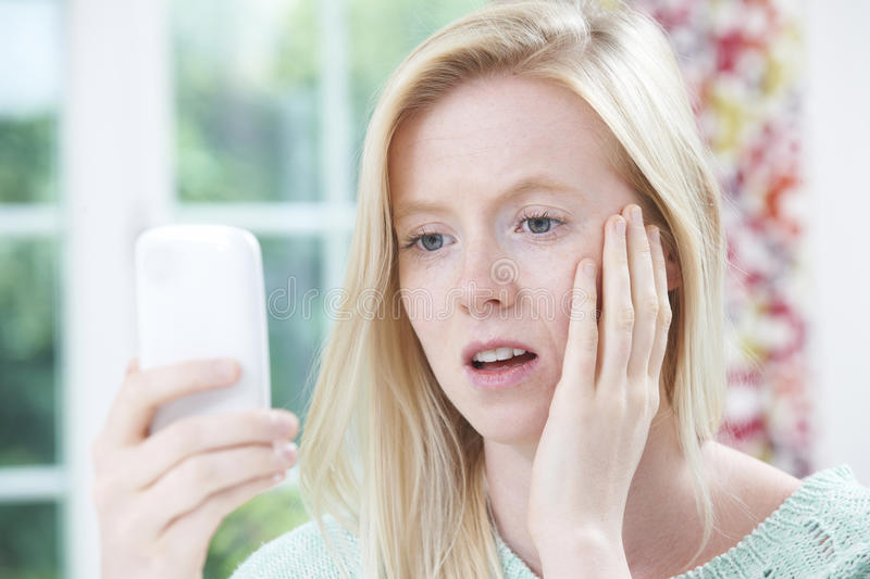 Teenage Girl Victim Of Bullying By Text Message. Upset Teenage Girl Victim Of Bullying By Text Message royalty free stock image