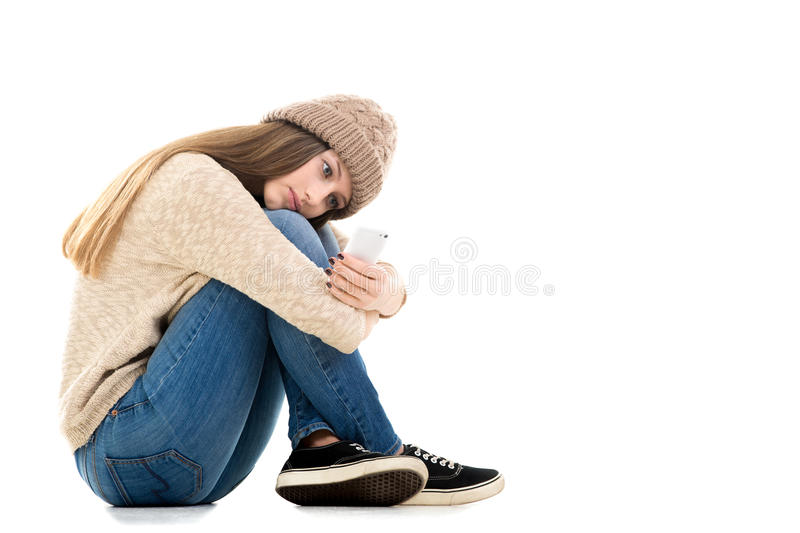 Teenage girl waiting for call with smartphone in her hands royalty free stock photo