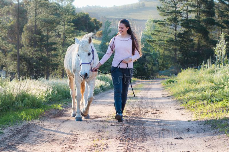 Teenage girl walking next to a white Boerperd horse on a dirt road royalty free stock photo