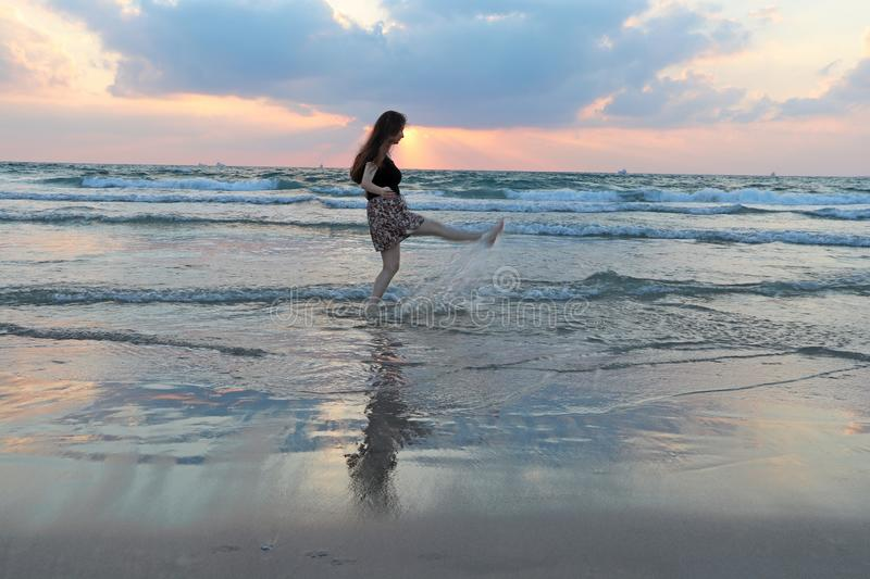 A teenage girl walks in the water at sunset royalty free stock image