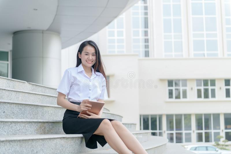 Teenage girl wearing uniform and using  tablet royalty free stock image
