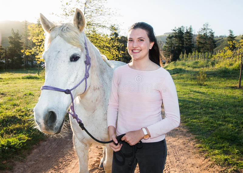 Teenage girl with a white Boerperd horse standing on a dirt road looking at the camera stock image