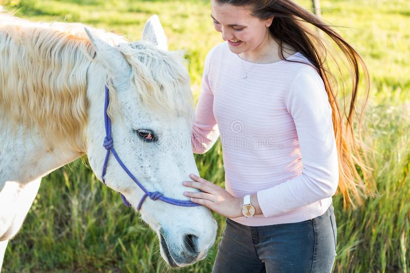 Teenage girl with a white Boerperd horse standing by his head petting his nose stock image