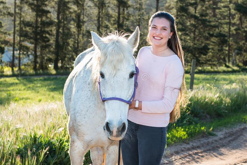 Teenage girl with a white Boerperd horse standing and looking at the camera royalty free stock photo