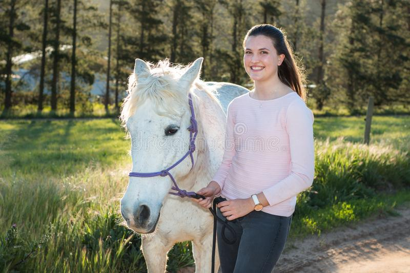 Teenage girl with a white Boerperd horse standing and looking at the camera stock image
