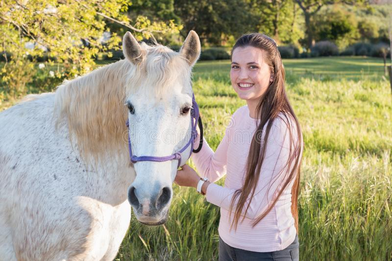 Teenage girl with a white Boerperd horse standing and looking at the camera royalty free stock image