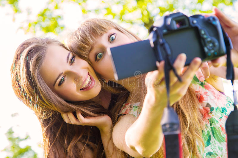 Girls taking selfie. Happy young blonde woman and teenage girl pulling face while taking a selfie using a DSLR camera using live view, bright background stock photos