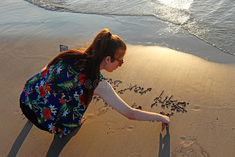 A teenage girl writes on the sand in the beach royalty free stock photography