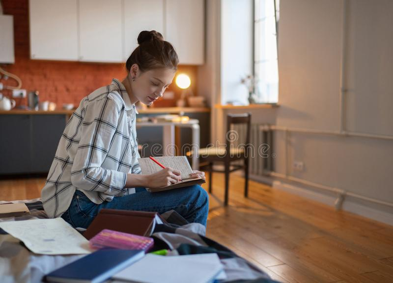 Teenage girl writing notes sitting on bed. Attractive concentrated teenage female student taking notes preparing for exam while sitting on bed royalty free stock images