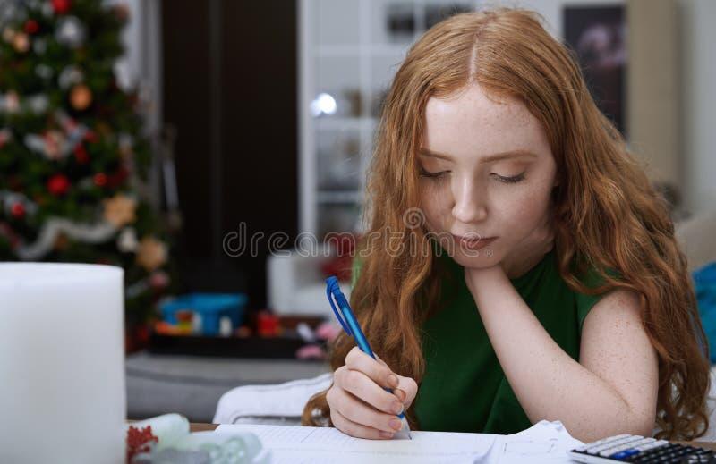 Teenage girl 13-15 years doing homework royalty free stock photos