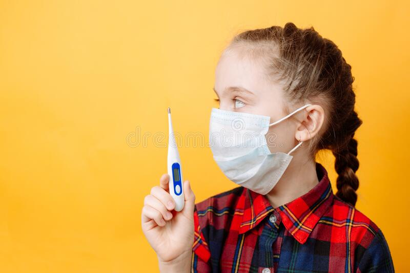 A Teenage girl on a Yellow Background Holds a Thermometer in her hand and Looks Away.  stock photos