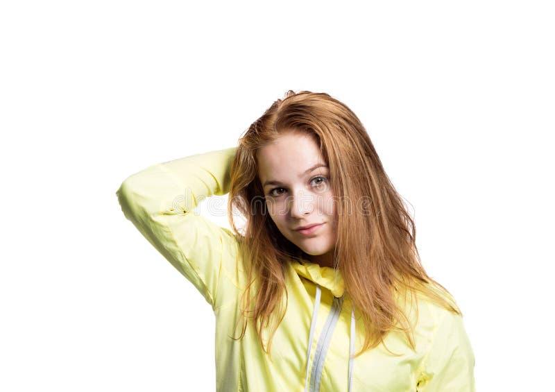 Teenage girl in yellow running jacket. Studio shot, isolated. royalty free stock photo