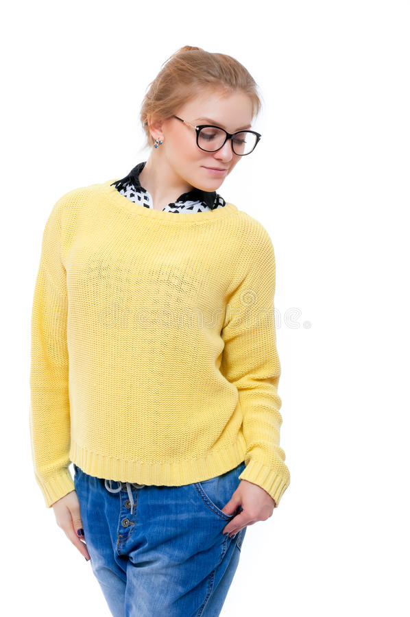 Teenage girl or young woman in yellow sweater and glasses. Looking down stock photo