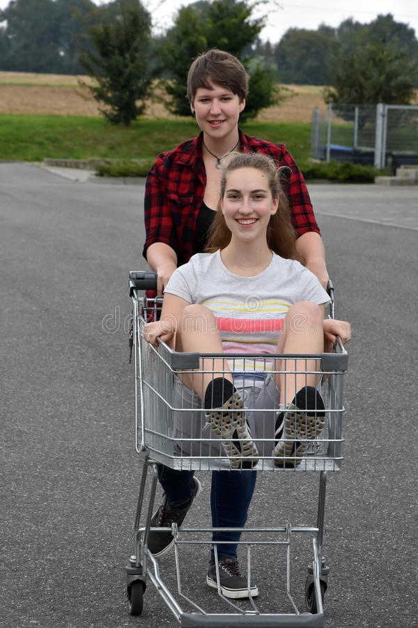 Teenage girlfriends with shopping cart royalty free stock photos