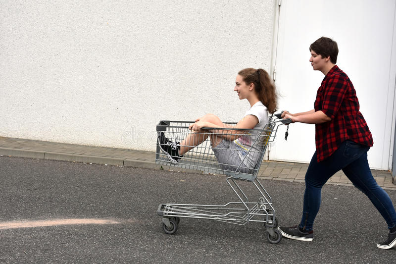 Teenage girlfriends with shopping cart royalty free stock image